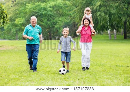 Happy Family Playing Soccer Game With Grandchildren Together In Park. Running For Ball