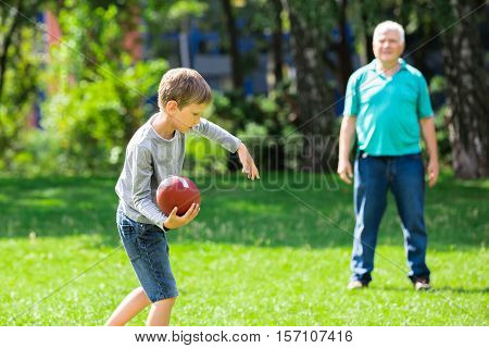 Kid Throwing Rugby Ball To Grandfather While Playing In The Park