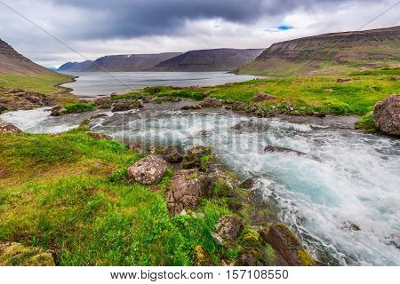 Mountain River Flowing Into The Lake Between The Mountains In Iceland