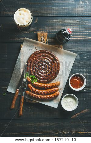 Grilled sausages with sauces and glass of dark beer on rustic wooden serving board over dark scorched wooden background, top view