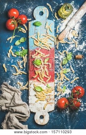 Ingredients for cooking Italian dinner. Fresh pasta casarecce, cherry-tomatoes, basil leaves and bottle of olive oil on colorful wooden board over dark blue background. Top view, vertical composition