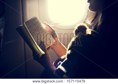 Woman Reading Writing Book Plane Concept