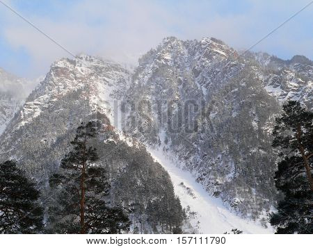 photo of a winter landscape with the prospect of snow-capped peaks in a mountain gorge in Russia (