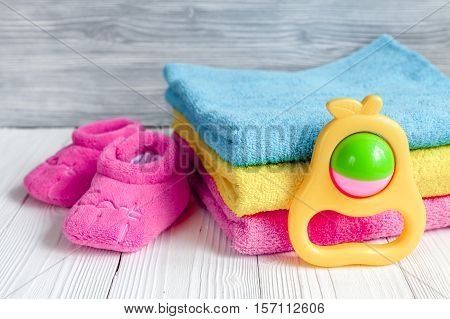 children's clothes and baby booties on wooden background top view