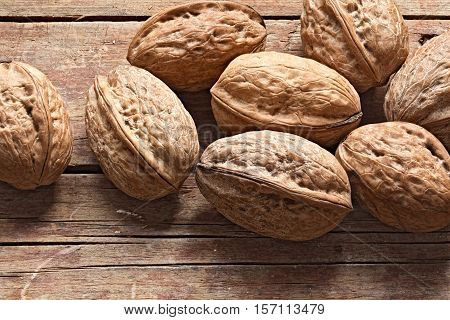 Whole unpeeled walnuts on a rough wooden background. Group of nuts in shell. Still life rustic photo.