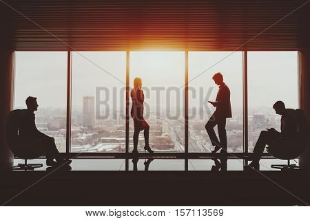 Silhouettes of businessman and businesswoman standing near window of skyscraper and two their male colleagues sitting on armchairs on opposite sides winter cityscape outside office interior