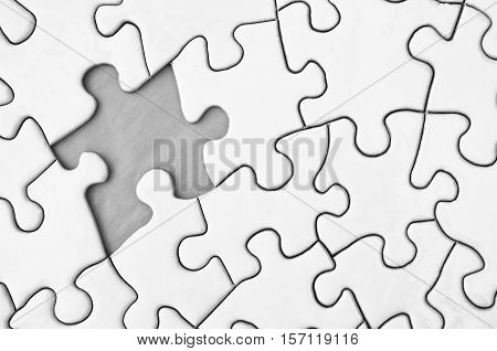 A close up image of a white jigsaw puzzle with a single piece missing.