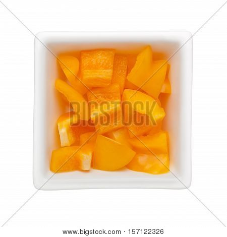 Diced yellow bell pepper in a square bowl isolated on white background