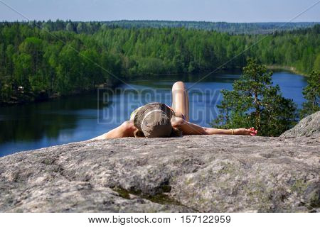 a woman laying on cliff an relaxing above the lake Yastrebinoye Priozersky district in Leningrad region Russia