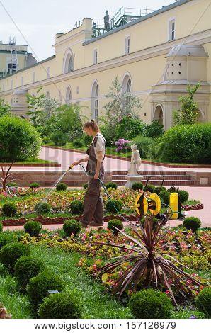 SAINT PETERSBURG RUSSIA - JUNE 05 205: a woman gardener watering flowers in the garden of Hermitage major art museum.