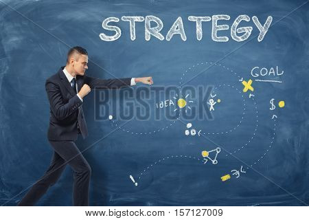 A businessman standing as if he is going to punch near the dark blue wall with the word 'strategy' and an action plan drawn on it. Modelling of business processes. Strategic planning. Football coach.