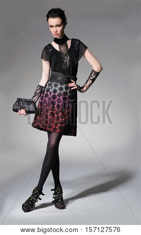 Full length fashion model in fashion dress holding purse posing in light background