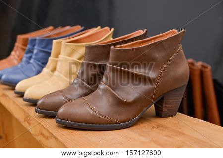 Women's leather boots on wooden table