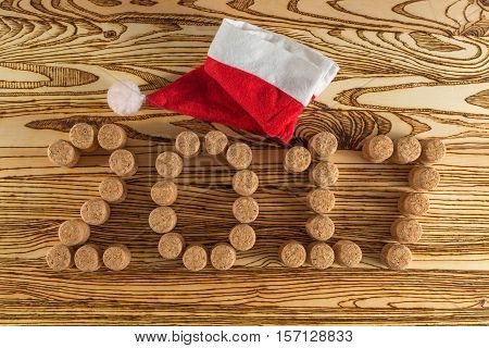 Inscription 2017 laid out champagne corks and a cap of Santa Claus on wooden table for background.