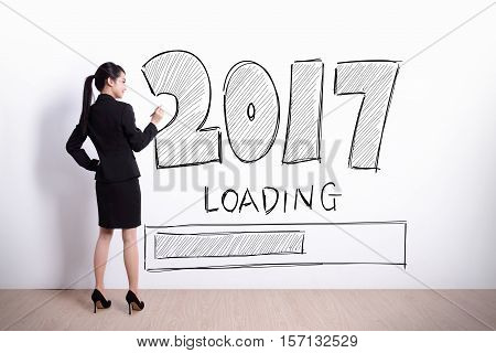 New Year is loading now - Back view of business woman writing 2017 new year on white wall background