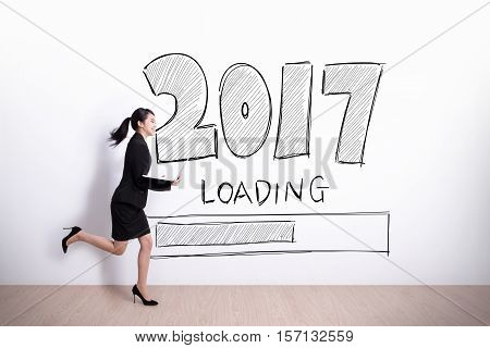 New Year is loading now - Successful business woman running and hold laptop computer with 2017 text and white wall background
