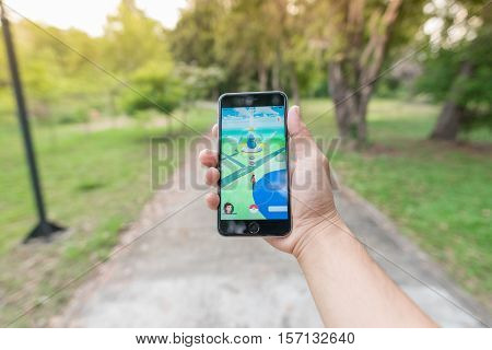 UBONRATCHATHANI THAILAND - OCTOBER 07 2016: Person holding mobile phone and playing Pokemon Go game. Pokemon Go is a location-based augmented reality mobile game.