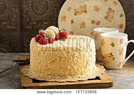 Napoleon cake with butterscotch frosting decorated with macarons
