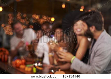 Young adults socialising at a party in a bar, defocussed