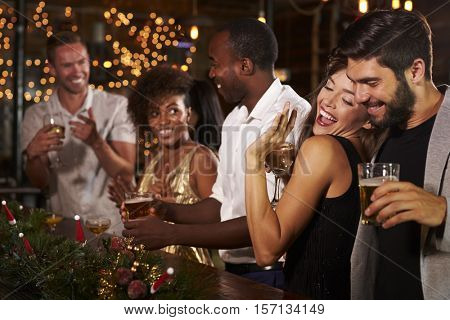 Friends having fun at a Christmas party in a bar