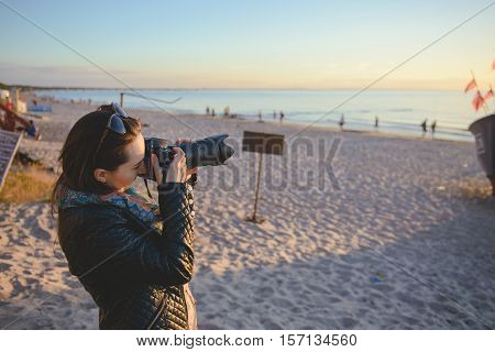 professional woman photographer on the beach summer time