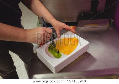 Worker painting a chocolate mould using colored chocolate in kitchen
