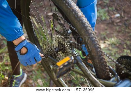 Close-up of male mountain biker fixing his bike chain in the forest