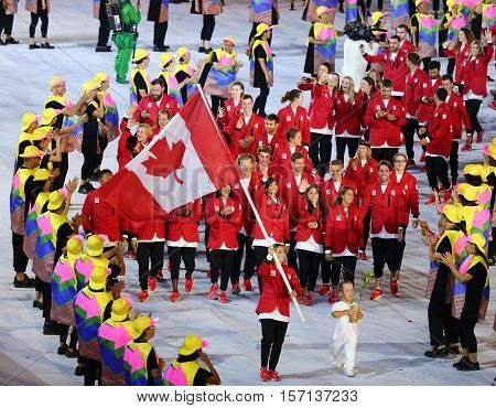 RIO DE JANEIRO, BRAZIL - AUGUST 5, 2016:Olympic champion trampoline gymnast Rosie MacLennan carrying Canadian flag leading the Olympic team Canada in the Rio 2016 Opening Ceremony at Maracana Stadium