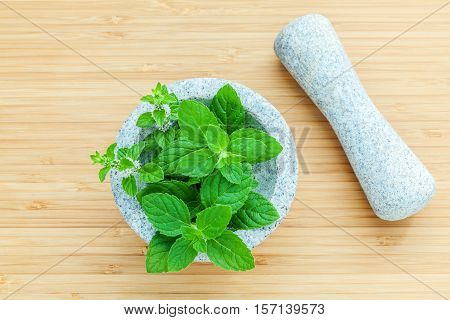Closeup Fresh Peppermint Leaves In The White Mortar On Bamboo Cutting Board . Food Ingredients And S