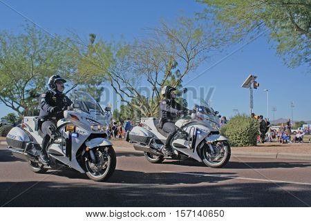 PHOENIX, AZ- NOV. 11: Two male police officers wearing helmets riding motorcycles in the City of Surprise, Arizona Veteran's Day Parade on November 11, 2016.