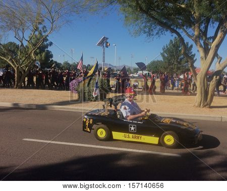 PHOENIX, AZ- NOV. 11: Male veteran driving a mini black car with machine gun, yellow-orange decals, yellow hubcaps and a yellow stripe with black letters stating U.S. Army at the Veteran's Day Parade in Surprise, Arizona on November 11, 2016.