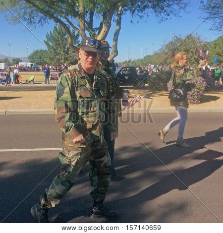 PHOENIX, AZ- NOV. 11: Male veteran wearing camouflage facing camera while walking in Veteran's Day Parade in Surprise, Arizona on November 11, 2016.