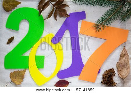 2017 new year. Colorful numbers on the background dry leaves and tree branches. this suggests that autumn is gone and winter comes and the new year