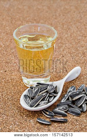 Bowl of sunflower oil and sunflower seeds on wooden background.