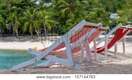Appealing Beach Chairs on Sand. Palm Trees and Ocean in Background. Haad Salat. Koh Pangang, Thailand.