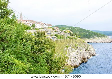 Vrbnik town on Krk island Croatia. View of Mediterranean medieval architecture the bell tower of the Parish church of the assumption of the blessed virgin mary beach coastline sea rocky cliffs and architecture.