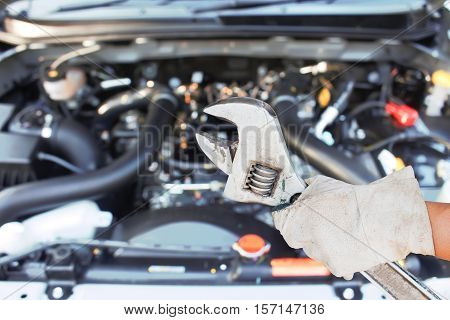 Hand with wrench checking car  new engine.