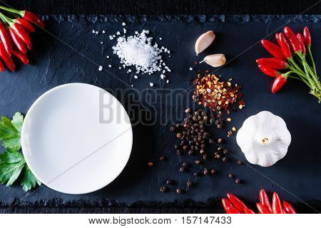 Dish, spices and vegetables on a black stone plate