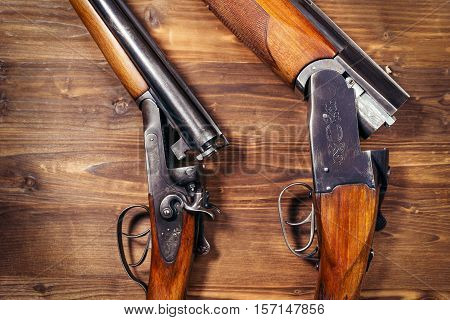 Old shotgun on the brown wooden background