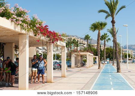 Altea, Spain - September 7, 2016: Tourists enjoying themselves  shade shelter on esplanade cycleway along waterfront in Altea, Spain.
