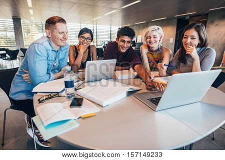 Multiethnic group of young people studying together at a table looking at laptop. Young students in cooperation with their school assignment.