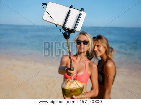 Two young female friends on the beach taking self portrait with mobile phone on selfie stick. Women on beach holiday taking selfie. Focus on smart phone attached to selfie stick.