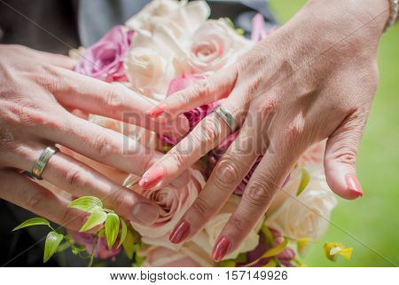 The groom and the bride place hands over a wedding bouquet. Wedding bouquet and wedding rings