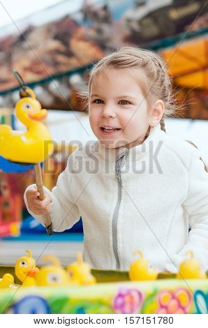 Beautiful girl in the amusement park to catch a toy duckling.
