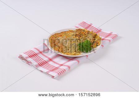 plate of freshly fried potato pancakes on checkered dishtowel