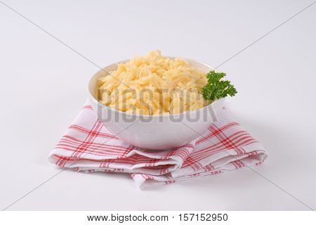 bowl of grated raw potatoes on checkered dishtowel
