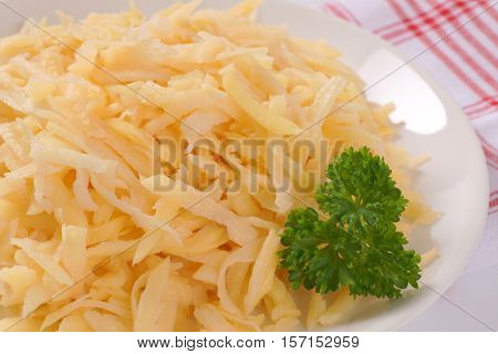 plate of grated raw potatoes on checkered dishtowel - close up