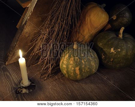 Retro grunge still life with broom, candle and pumpkins by staircase. Occult or esoteric concept with magic objects, mystic ritual