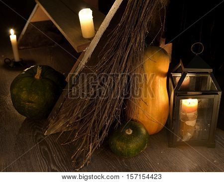 Scary mystic still life with witch broomstick, pumpkins and candles by staircase. Occult or esoteric ritual with magic objects, Halloween background