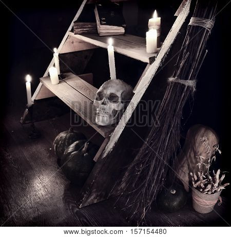 Scary mystic ritual with human skull, candles and evil staircase in witch house. Occult or esoteric still life with magic objects, Halloween background